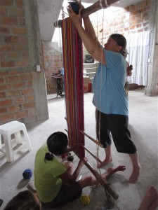 Passing ball of yarn front to back over upper loom bar.